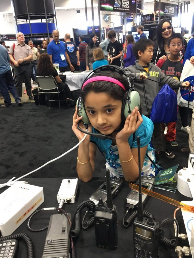 Girl with headphones communicating via Amateur Radio ARISS